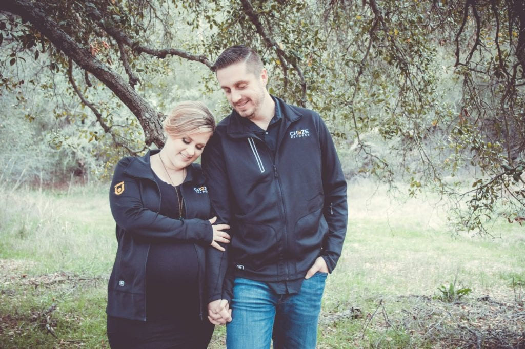 Team members Nathan and Julia Muzquiz wear Chuze Fitness jackets for maternity photos.